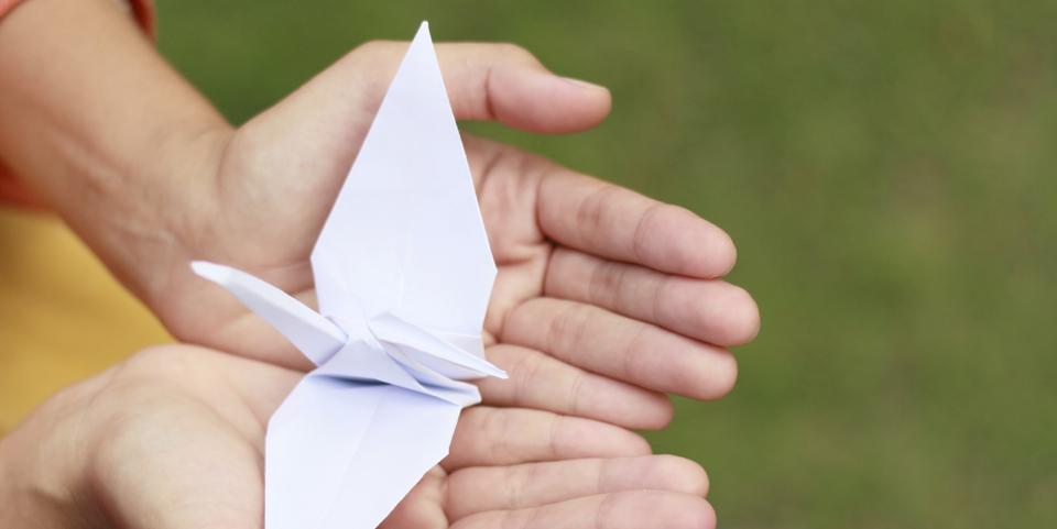 origami kraanvogel in handen