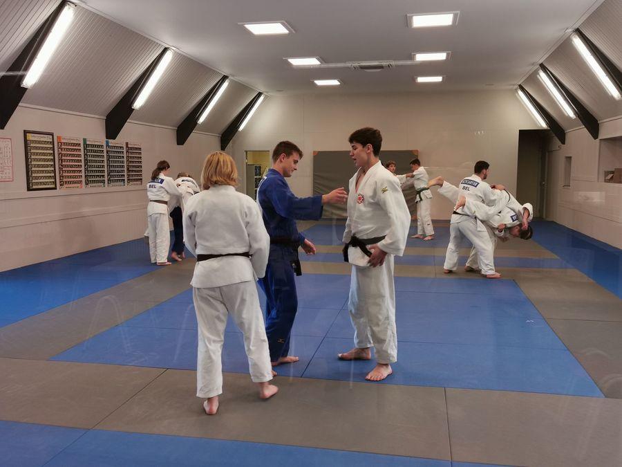 Een aantal mensen doet aan gevechtsport in een afgesloten ruimte.