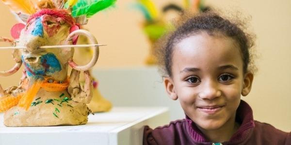 Kind poseert naast kunstwerkje