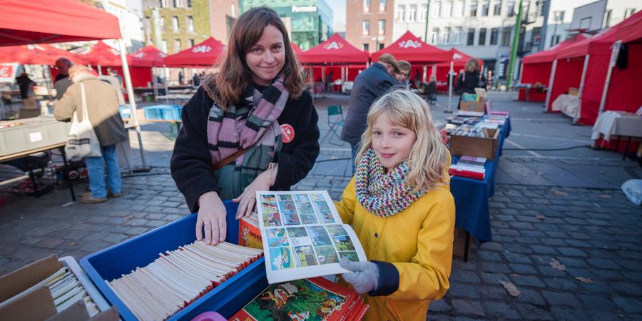 Een meisje en haar mama tonen een Suske en Wiske-album.