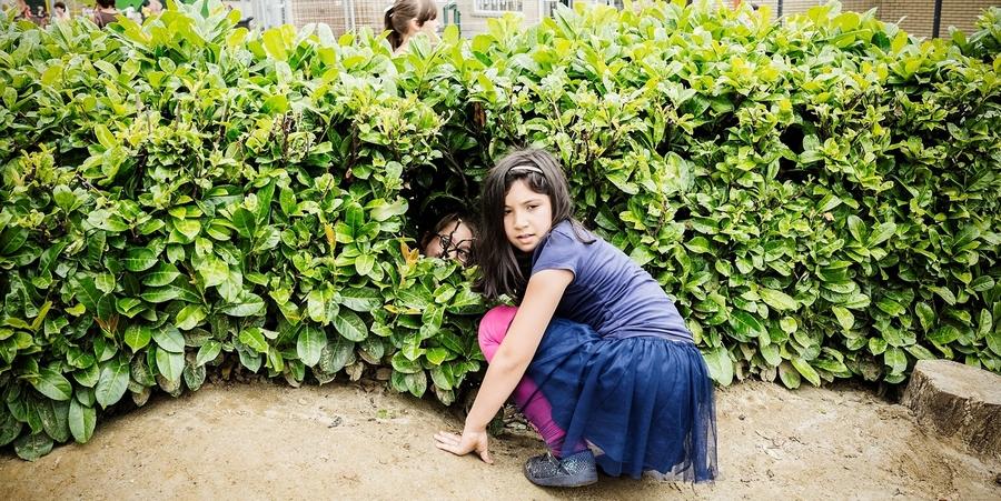 Meisje zit verstopt in een haag