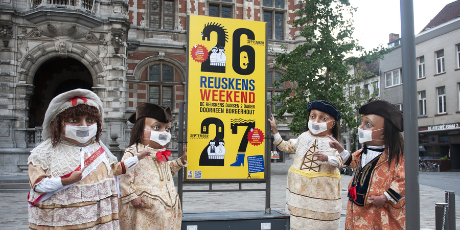 Vier Reuskens staan rond een bord met praktische info over het Reuskensweekend. Op de achtergrond het districtshuis van Borgerhout.