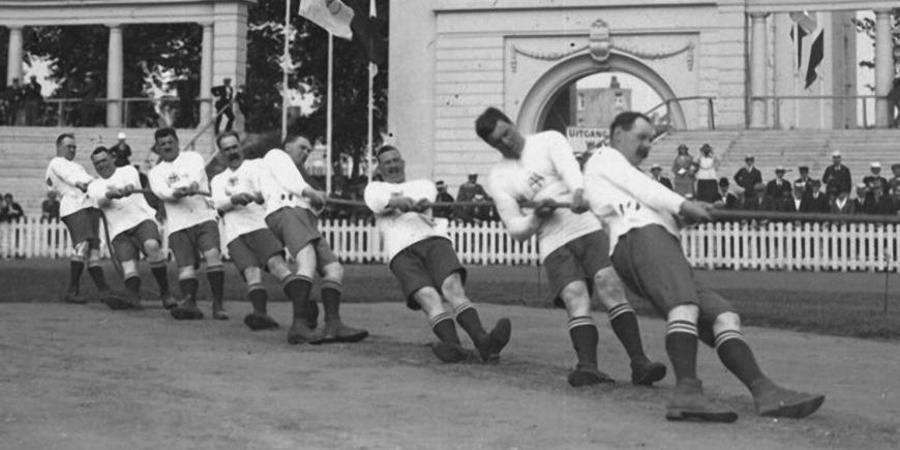 Touwtrekken tijdens Olympische Spelen 1920 met olympische poort op de achtergrond