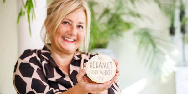 Dame toont haar zelfgemaakte koekje met tekst op