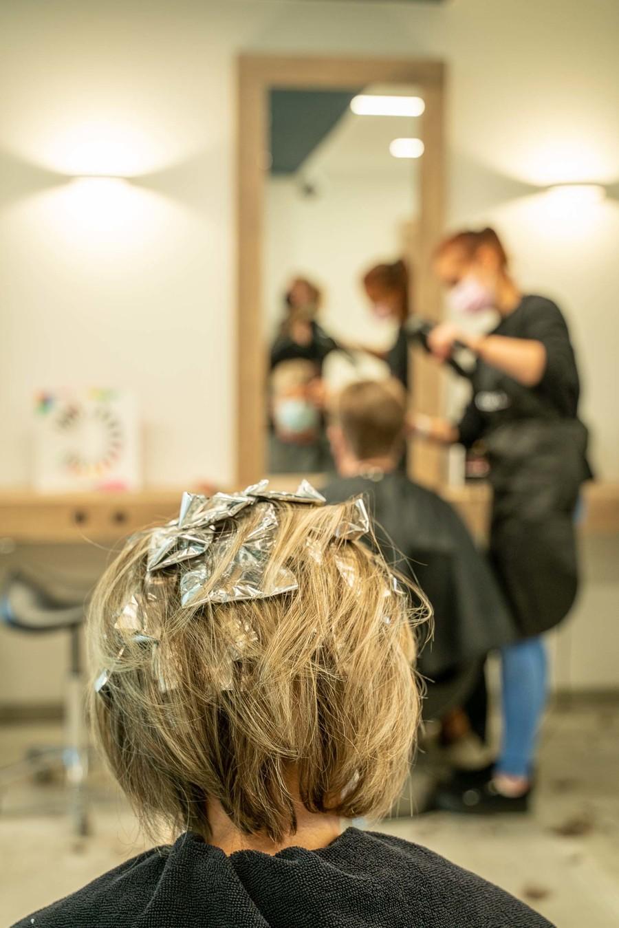 Vrouw met aluminiumpakjes in de haren