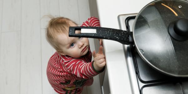Een jong kindje wil een pan van het kookvuur halen.