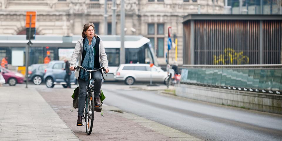 Vrouw fietst naar het werk in Antwerpen