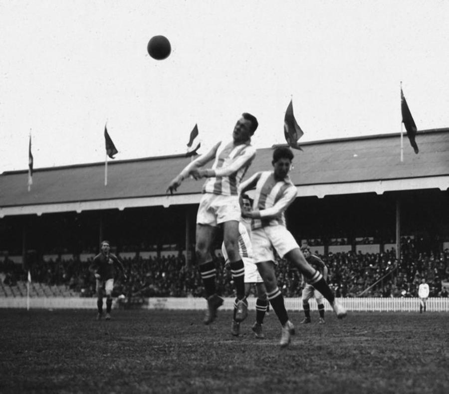 Sfeerbeeld voetbalmatch Olympische Spelen 1920: kopbalduel tussen 2 spelers