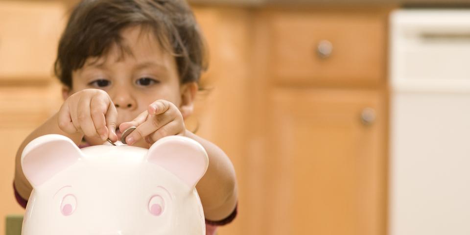 Een kindje steekt muntstukjes in een spaarvarken.