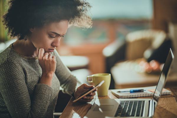 Vrouw kijkt op haar smartphone met haar laptop op tafel.