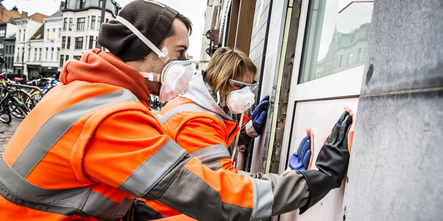 graffiti wordt verwijderd door twee stadsmedewerkers