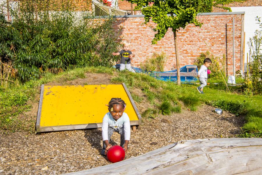 De heuvel met glijplaat in een zone van houtsnippers. Een meisje speelt met een bal.