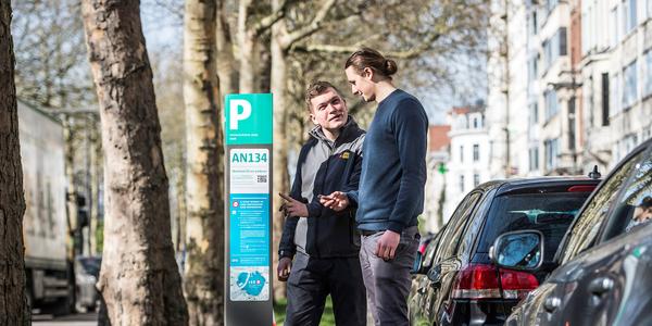 Parkeerwachter en burger staan voor een parkeerautomaat.