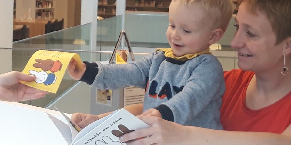 Peuter geeft een voucher af in ruil voor een gratis boekje