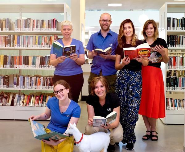 Zes medewerkers van Bibliotheek Bist temidden kasten vol boeken.