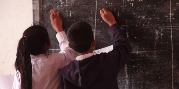 Twee kinderen schrijven op een schoolbord.