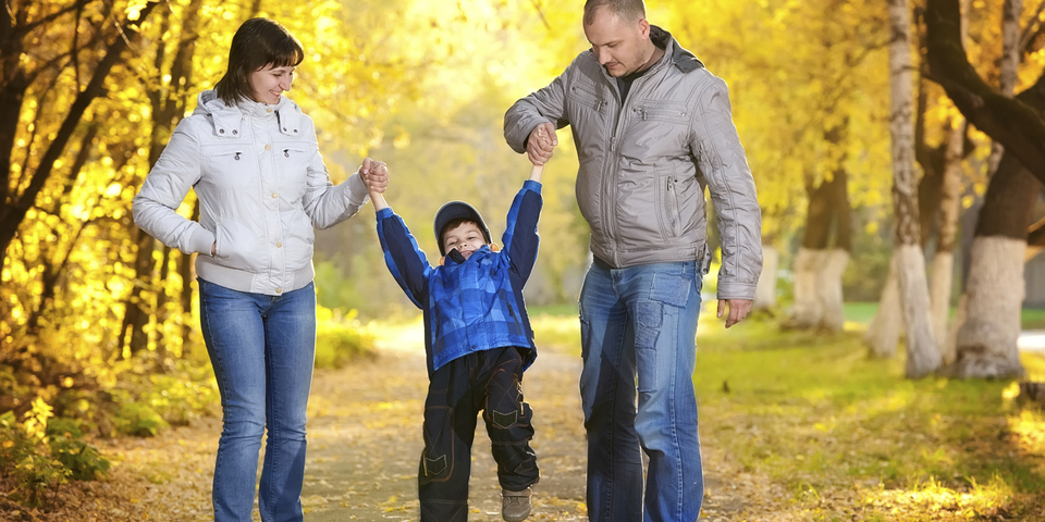 Twee ouders wandelen al spelend met hun zoon