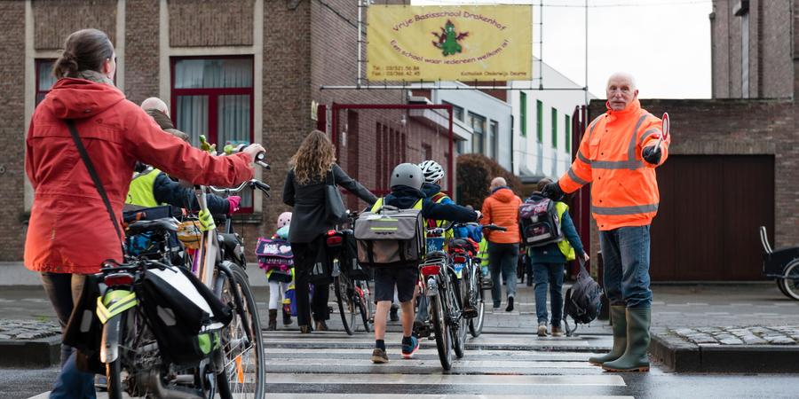 Ouders en leerlingen steken het zebrapad over voor de school