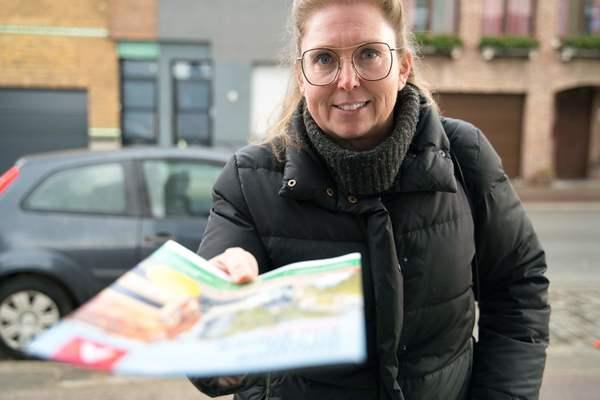 Vrouw die magazine in de brievenbus stopt