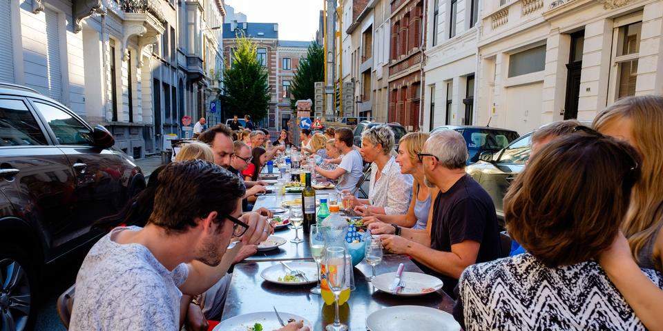 Buren die samen eten aan een lange tafel op straat
