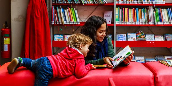 Moeder en kind lezen samen een boek in bibliotheek Permeke