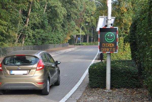 Een auto rijdt op het Laar een snelheidsinformatiebord voorbij dat een groene lachende smiley laat zien, met daaronder Ekeren dankt u