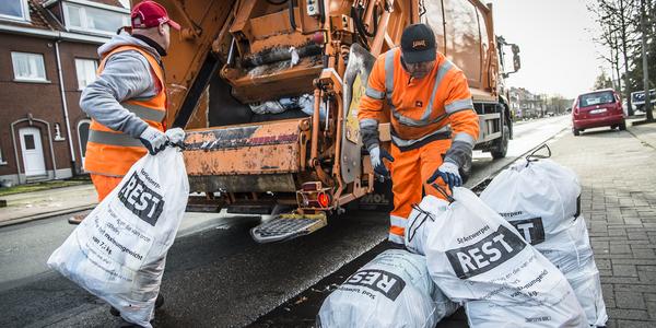 vuilnismannen die zakken in een vuilniswagen gooien