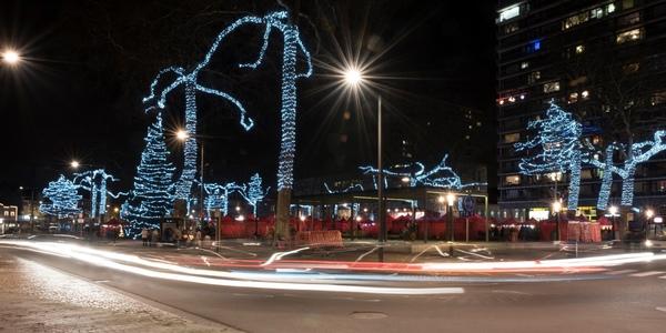 Een nachtbeeld van de met lichtjesslingers versierde bomen van het Wilrijkse centrumplein Bist.