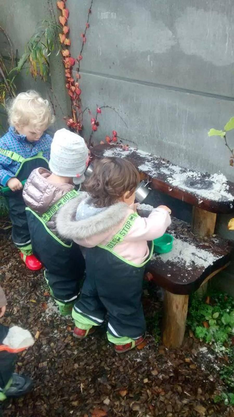 Kinderen spelen in regenbroek en warme kleren in de buitenkeuken