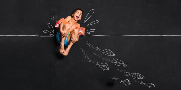 Springende jongen met zwembandjes