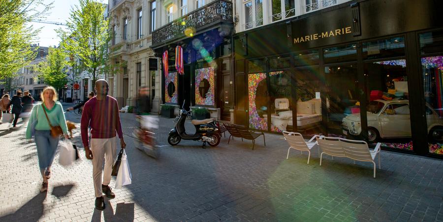 Een vrouw en een man winkelen in een winkelstraat in Antwerpen.