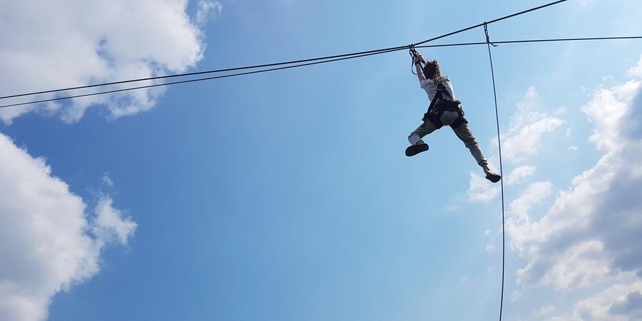 Een kind komt naar beneden langs een death ride kabel.