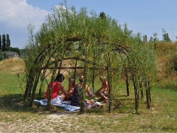 Een gezin picknickt in een wilgenhut