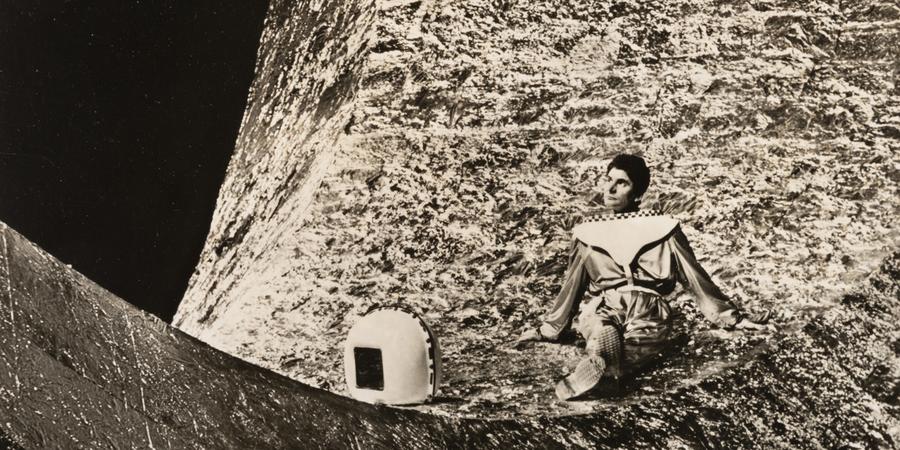 Foto van een man die zit op iets wat de maan moet voorstellen.