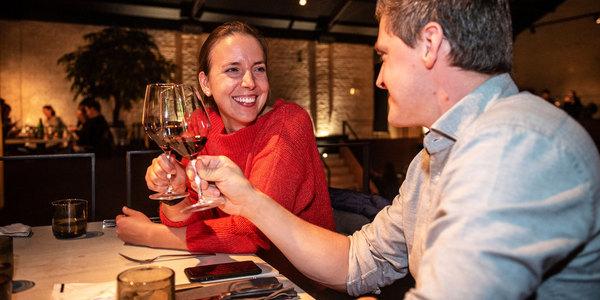 Vrouw en man klinken met een glas wijn op restaurant.