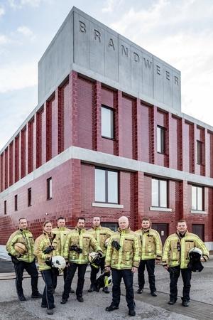 8 brandweerlieden in interventiekledij voor de brandweerkazerne.