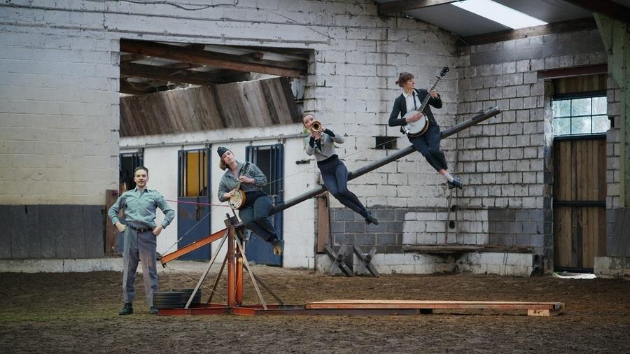 Vier artiesten zitten op een slagboom en spelen muziek