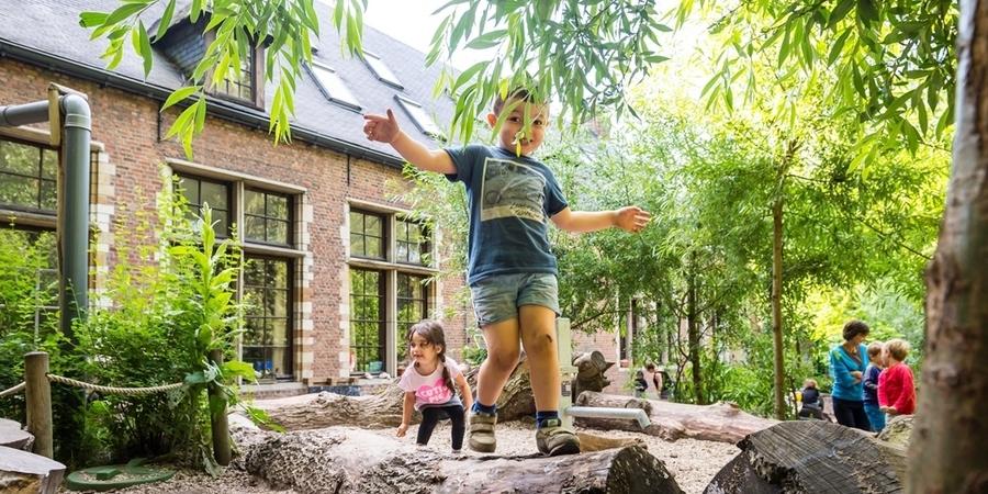 Een jongetje loopt over een boomstam op een klimaatrobuuste natuurspeelplaats