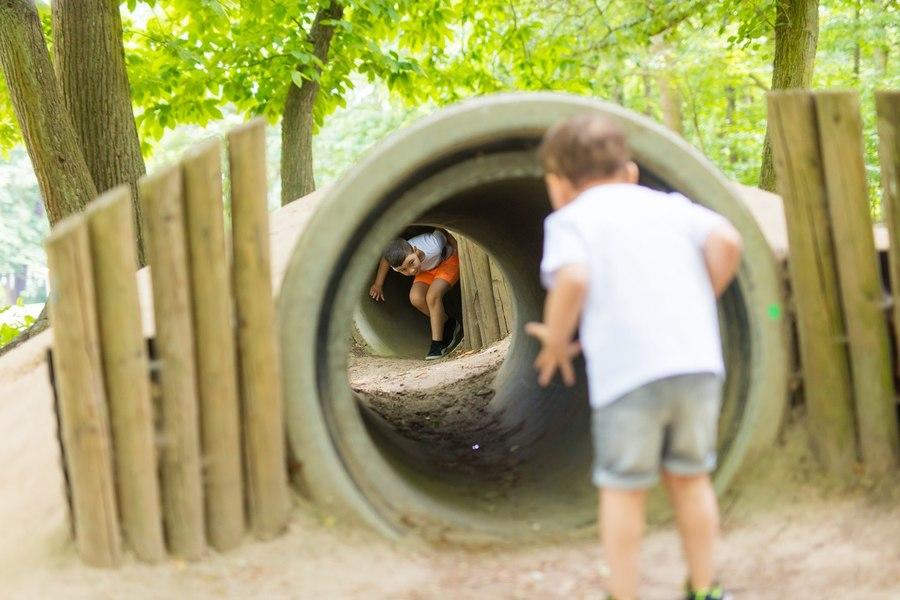 Kinderen spelen in buizen aan de Bossafari