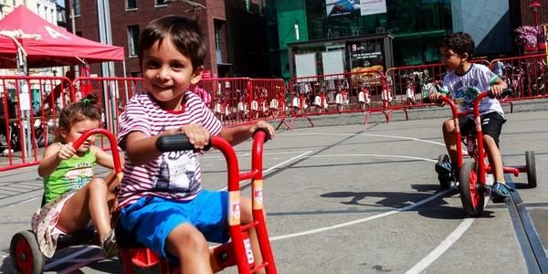 kleuters fietsen op een hindernissenparcours op het De Coninckplein in Antwerpen met bibliotheek Permeke op de achtergrond