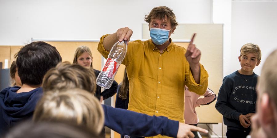 een begeleider met mondmasker geeft les aan kinderen