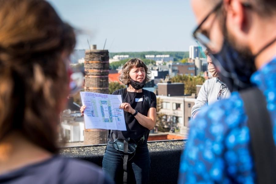 Een vrouw toont een bouwplan op het dak van een appartementsgebouw