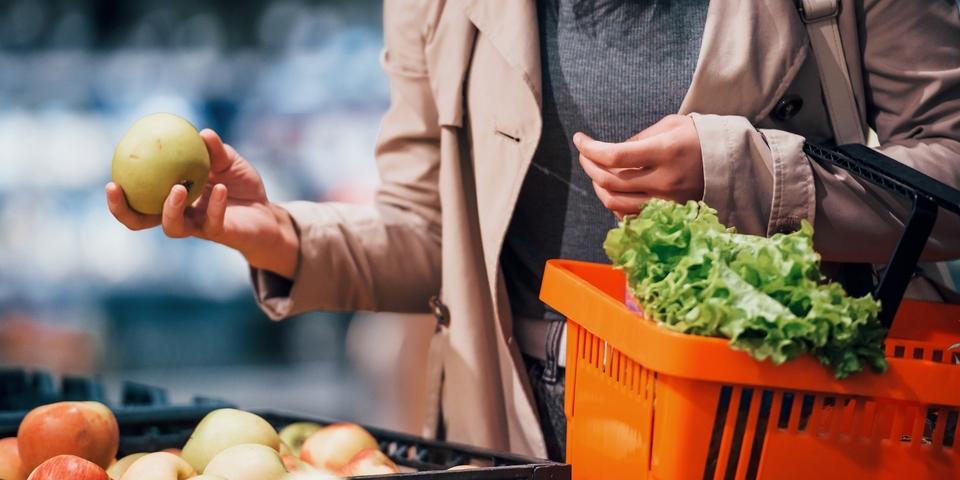 Een detailbeeld uit een supermarkt, waarbij een hand een appel vasthoudt.