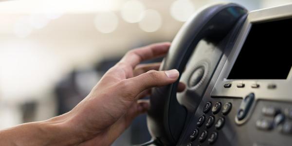 Een hand neemt een telefoon op.