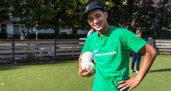 Een voetballer op een pleintje in de stad.