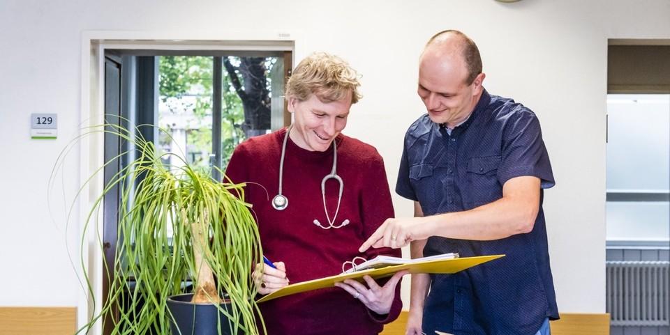 een arts en medewerker in gesprek