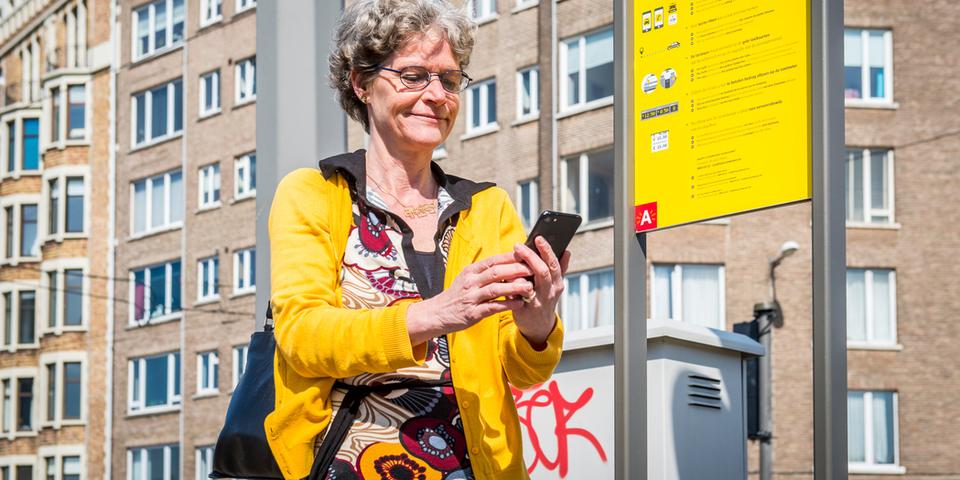 Een vrouw kijkt op haar smartphone terwijl ze naast een taxistand staat.