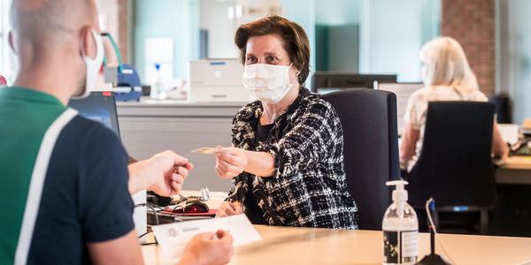 Een klant van een stadsloket geeft haar identiteitsbewijs aan een loketmedewerker. Beiden dragen een mondmasker.