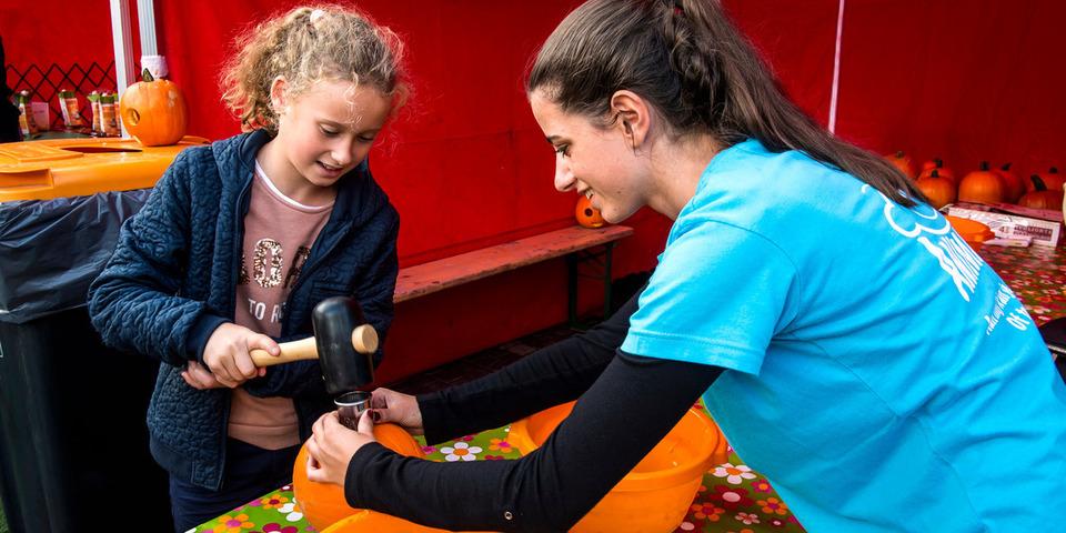 Een meisje speelt aan een speelkraam.
