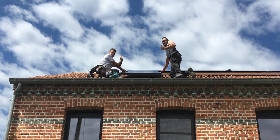 Twee mannen plaatsen zonnepanelen op een dak